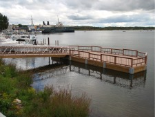 Photo of the Universally Accessible Arthur St Fishing Pier on Manistee Lake that shows the large fishing area with the S.S. City of Milwaukee car ferry in the background